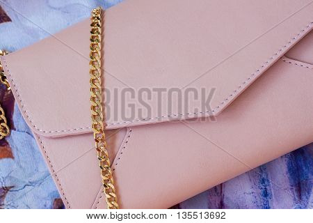 Pink envelope purse , decorated with gold chain close-up as background with space for your logo or text.