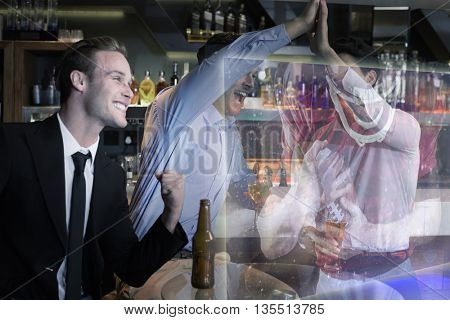 Handsome friends having a drink together against composite image of american football player protecting football