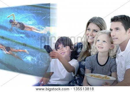 Smiling family watching a film at television against female swimmers racing in the swimming pool