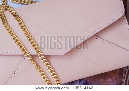 Pink clutch in form of an envelope, decorated with gold chain close-up as background.