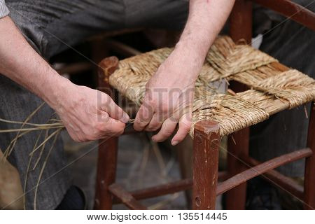Hands Of Elder Repairer Of Chairs Along The Street
