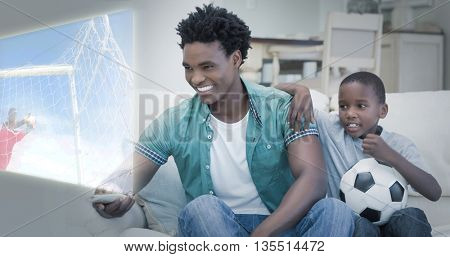 Composite image of father and son are watching sport on television at home