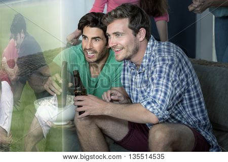 Composite image of friends are watching rugby match on television at home