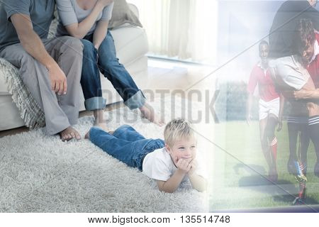 Composite image of cute boy lying on carpet is watching sport on television in front of his parents at home
