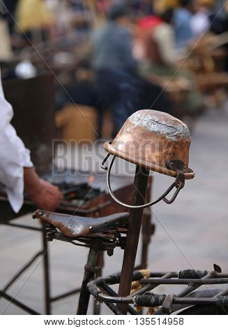 Old Copper Cauldron And An Antique Bicycle Saddle