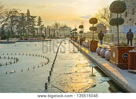 ANKARA TURKEY - JANUARY 16 2015: The winter sunset over the Haci Bayram Square with the frozen pond reflecting the sun beams on January 16 in Ankara.