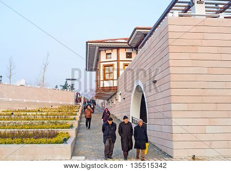 ANKARA TURKEY - JANUARY 16 2015: The tourists and locals leave the Haci Bayram Mosque walking along the modern street with green flower beds on January 16 in Ankara.