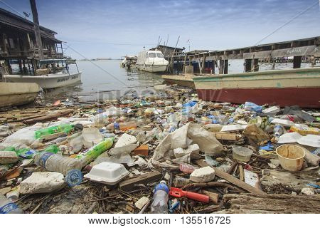 SANDAKAN, MALAYSIA - 23 JUNE 2016: Pollution of environment. Plastic rubbish washes up on beach in Asian fishing village, contaminating seafood.