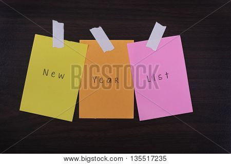 Motivational Concept Image of message note paper pinned on cork board with New Year List words written on it