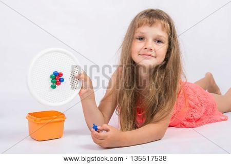 Girl Shows A Mosaic With Unfinished Flower
