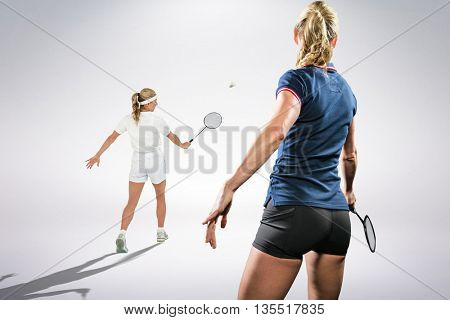 Composite image of badminton players playing badminton against white background