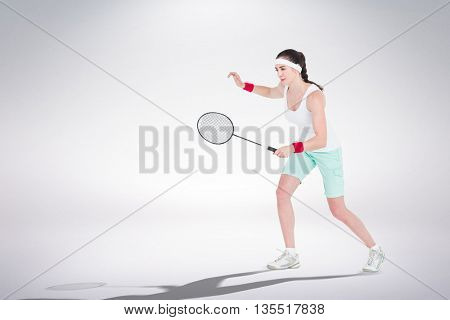 Composite image of female athlete playing badminton against white background
