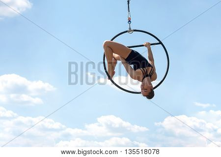 Sport woman doing exercises with a hoop outdoor against the blue sky. Sports equipment and lifestyle concept. Antigravity yoga.