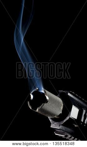 Firearm that has smoke coming from its barrel on a black background