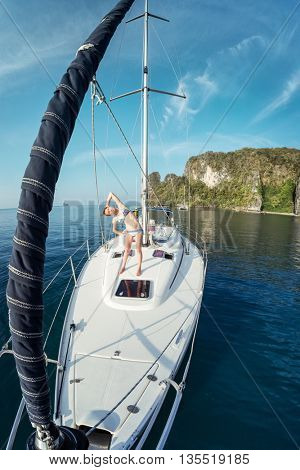 Young lady does exercise on the deck of the yacht anchored in the sea, Thailand