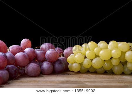 bunches of white and red grapes on wooden table