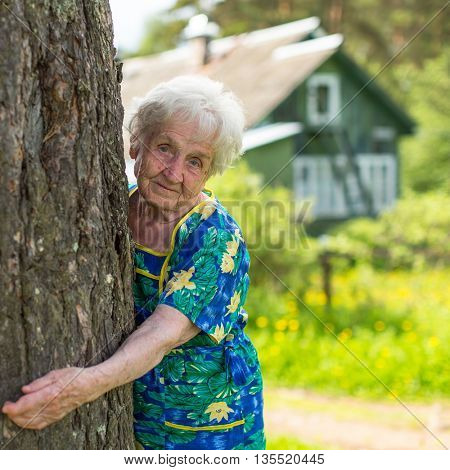 Grandma hugging a tree near rural home.