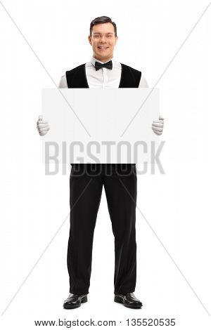 Full length portrait of a young butler holding a bank white signboard isolated on white background