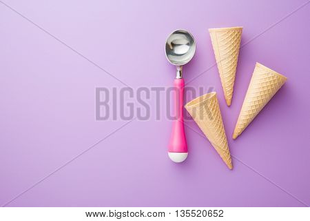 wafer cone and ice cream scoop on violet background. Top view.