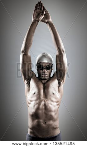 Composite image of swimmer ready to dive against grey background