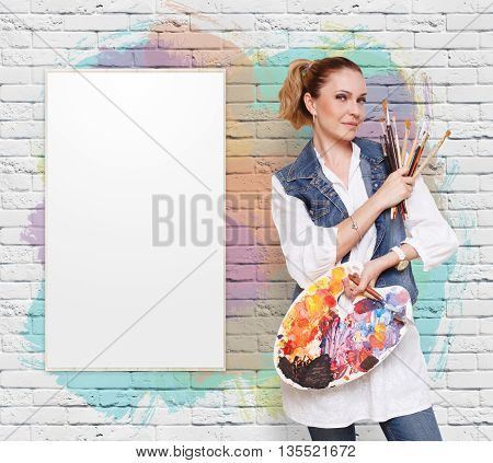 Happy artist. Woman with art tools. Female painter with brushes and palette. Empty picture at colorful brick wall with copy space. Fine art. Art classes for adults, education concept.