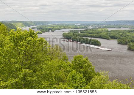 A scenic view of the Mississippi River with barges.