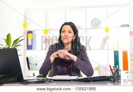 Young businesswoman sitting at workplace in her office