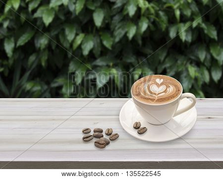 warm cup of coffee latte art with heart pattern in a white cup and coffee beans on wooden nature background.