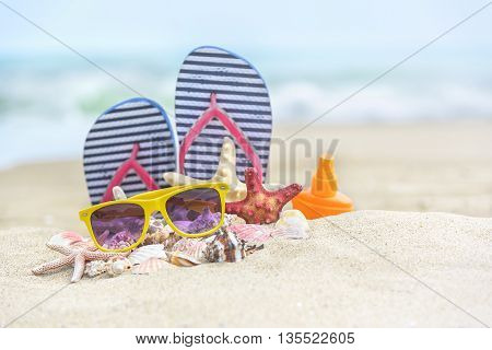 Flip-flops and shells on the beach. Summer Still Life.