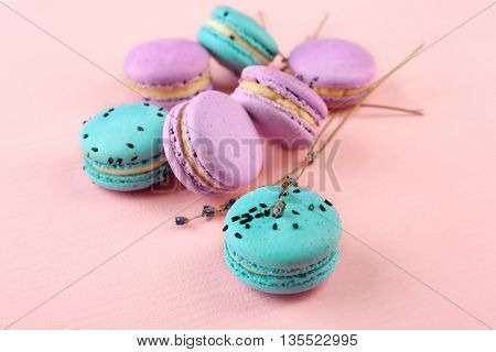 Tasty macaroons with twigs on pink background