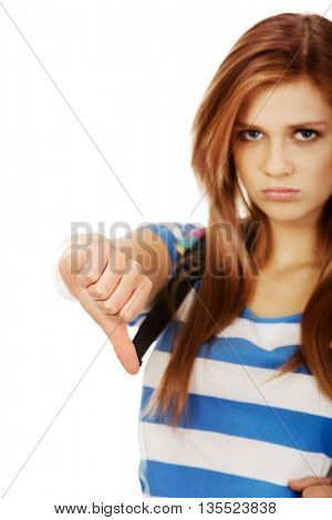 Young unhappy teenage woman shows thumbs down