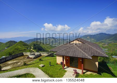 Beautiful little house on top of the hill with lovely blues sky and dramatic cloud formation