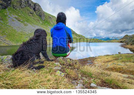 Girl looks like a mountain lake scene with his dog