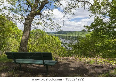A scenic view of the Mississippi River with a park bench.