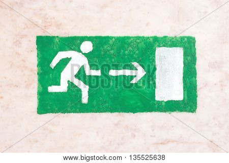 Emergency exit sign, green on a light background, visitor safety, the guests and participants