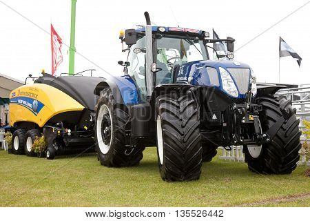 NEWBURY, UK - SEPTEMBER 21: A New Holland tractor and other agricultural machinery is displayed at the Berks County show as part of the events commercial activities on September 21, 2013 in Newbury