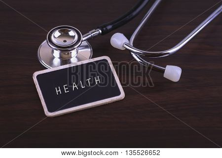 Medical Concept-Health words written on label tag with Stethoscope on wood background