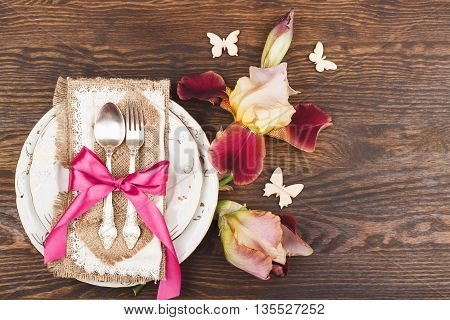 Table serving: Tableware with Irises and silverware on the wooden background