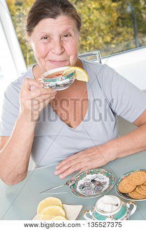 Cute elderly woman drinks tea sitting at the table. Studio photography in bright tones.