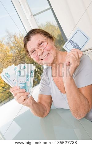 Happy elderly woman shows a stack of Russian money and passbook.