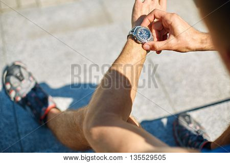 Man athlete doing running and watching the watch in park