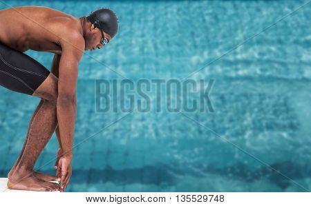 Swimmer ready to dive against view of swimming pool