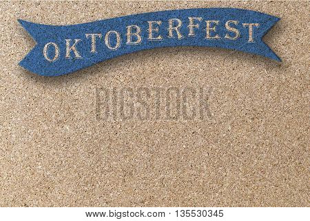 oktoberfest on blue ribbon on corkboard background
