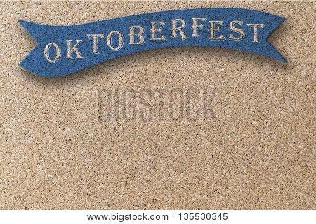 oktoberfest on blue ribbon on corkboard background