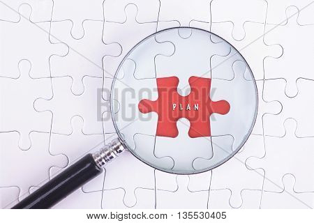 Business Concept - Magnifier Glass on white puzze with PLAN Word