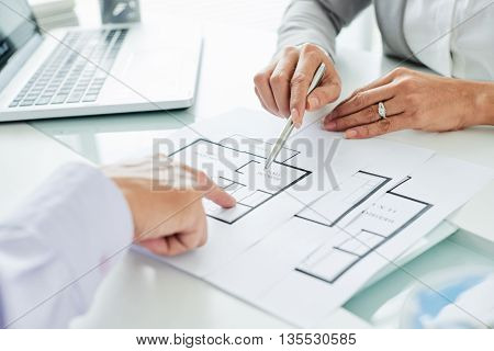 Realtor showing the plan of apartment to her client