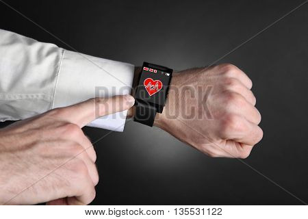 Male hands with heart icon on smart watch on dark background
