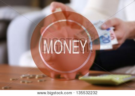 Money icon. Young man with piggy bank on wooden table.