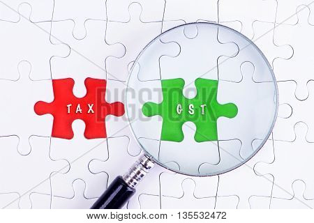 BUSINESS CONCEPT - Magnifying glass on missing puzzle with a word TAX AND GST