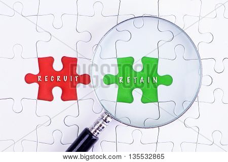 BUSINESS CONCEPT - Magnifying glass on missing puzzle with a word RECRUIT AND RETAIN